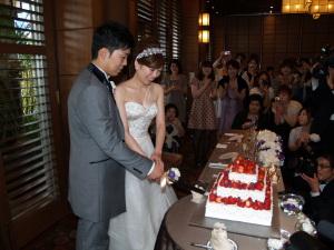ウェディングケーキにナイフを入れる新郎新婦